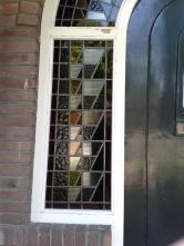 Hier is het raam gerestaureerd en terug in het kozijn gezet.